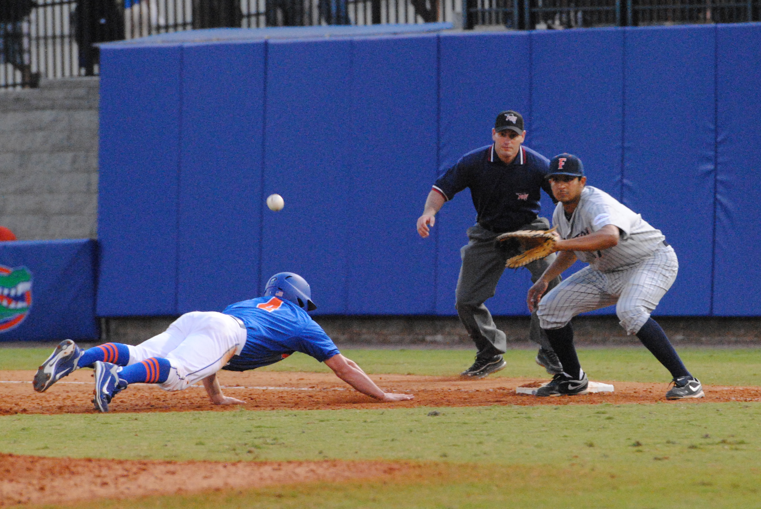 Junior Nolan Fontana dives into first base after leading off.