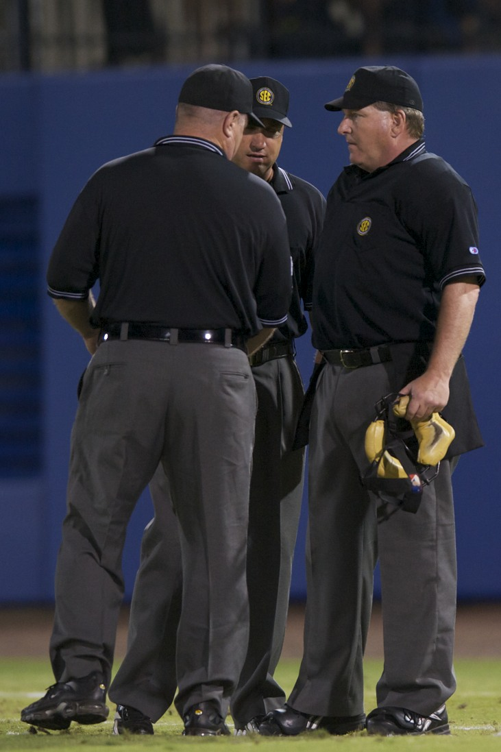 The umpires discussed a controversial call on whether a ball was caught off of a bounce off the ground, or the Georgia Pitcher's shoe.
