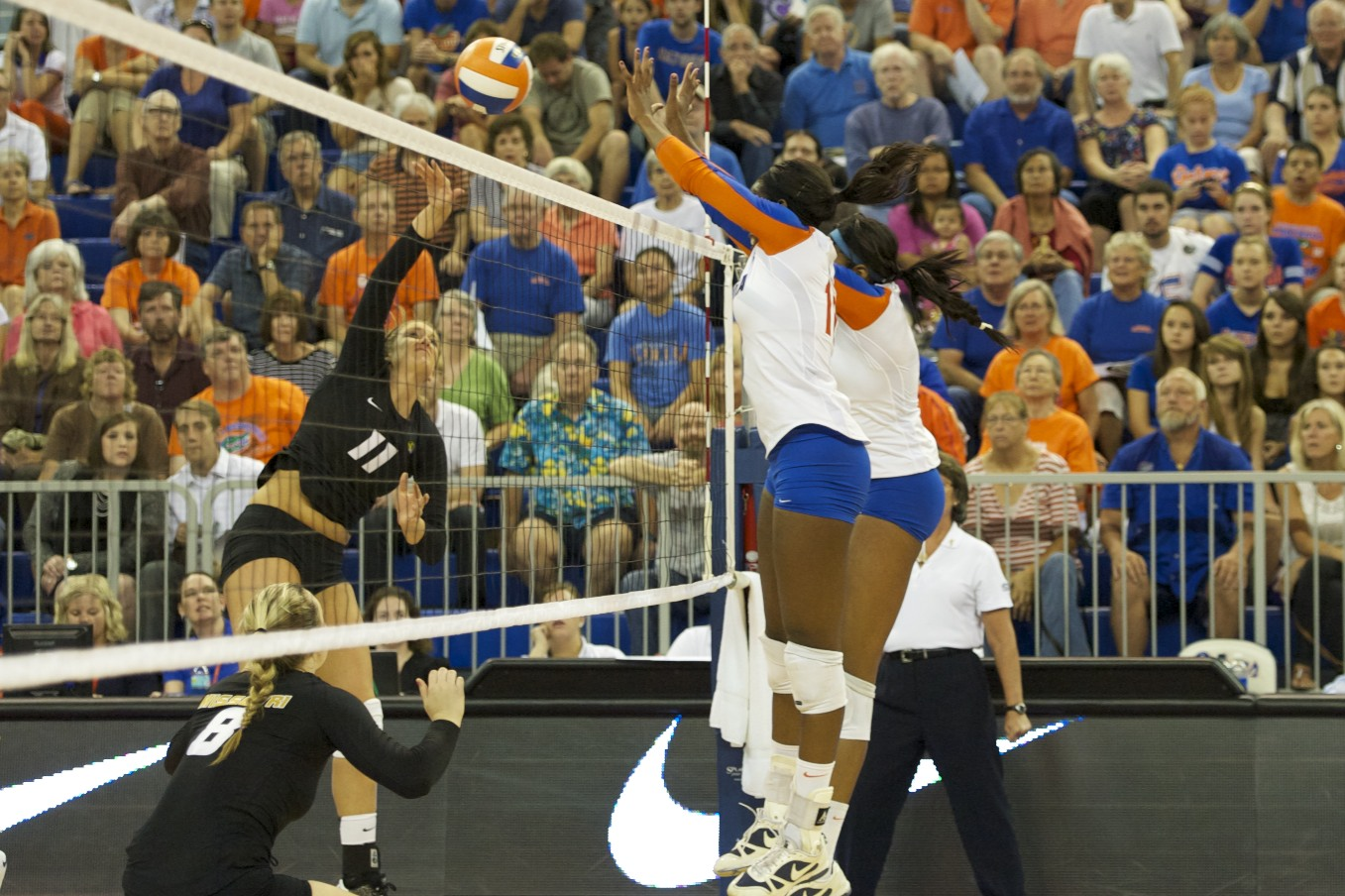 Chloe Mann and Tangerine Wiggs block Missouri hitter in the first set on Friday night.