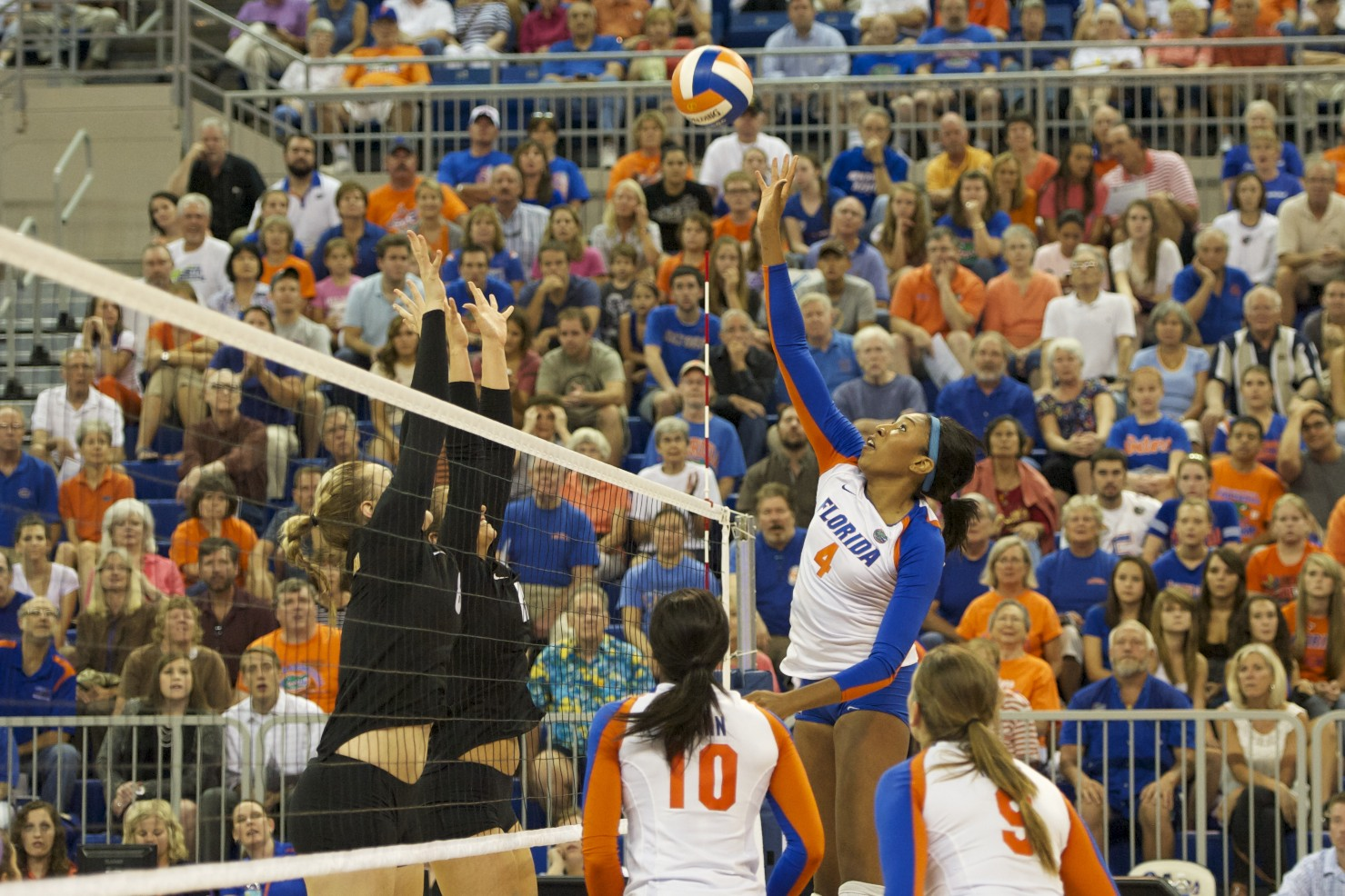 Senior Tangerine Wiggs tips the ball over the block for a point for the Florida Gators in the first set during the Friday night match.