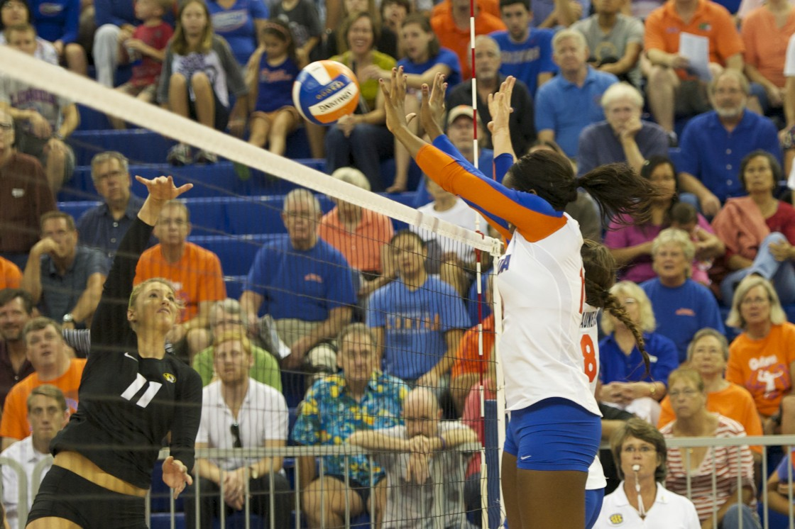 Tangerine Wiggs and Chloe Mann block Missouri hitter in the third set on Friday night.