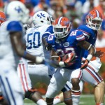Quarterback Jeff Driskel hands off the ball to running back Mike Gillislee for a gain of yards.