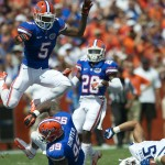 After a tackle, Marcus Roberson of the Florida Gators leaps over both teammates and opponents to avoid falling after the whistle.