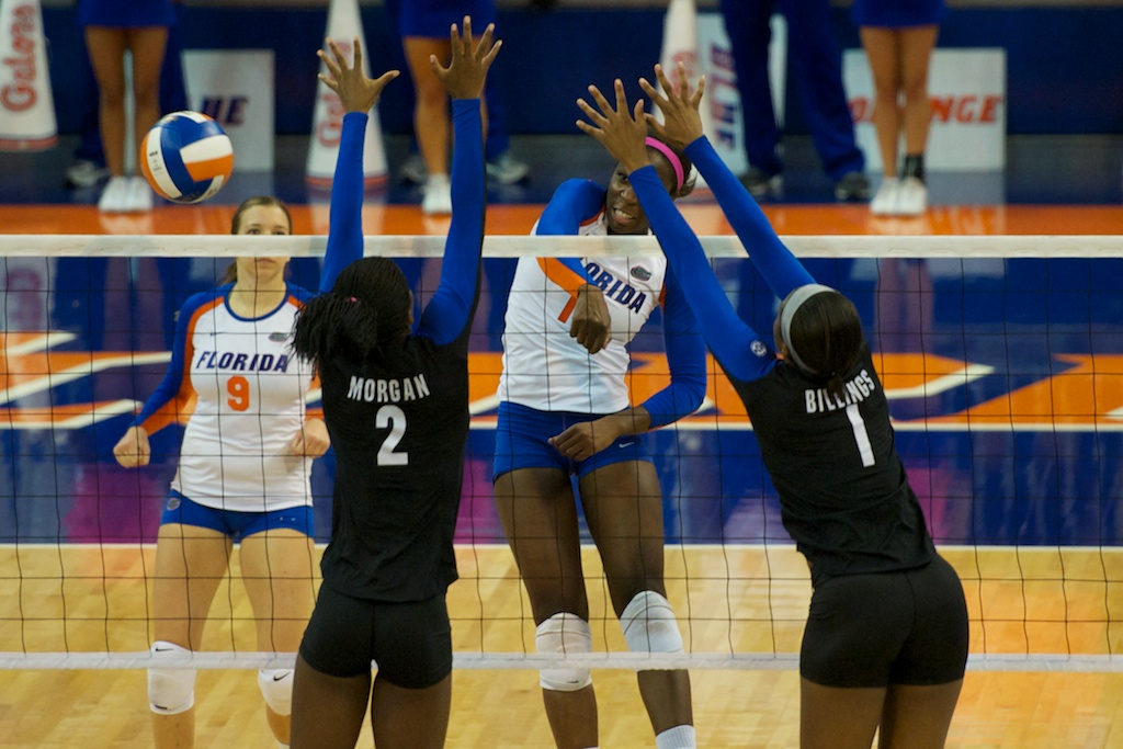 Middle blocker Chloe Mann gets a kill for the Gators in the second set of Sunday's match by hitting around the double block set up by Kentucky.