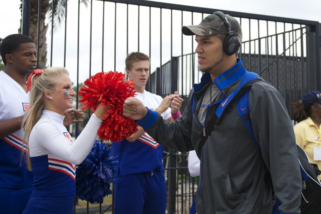 Trey Burton fist-bumps a cheerleader during Gator Walk.