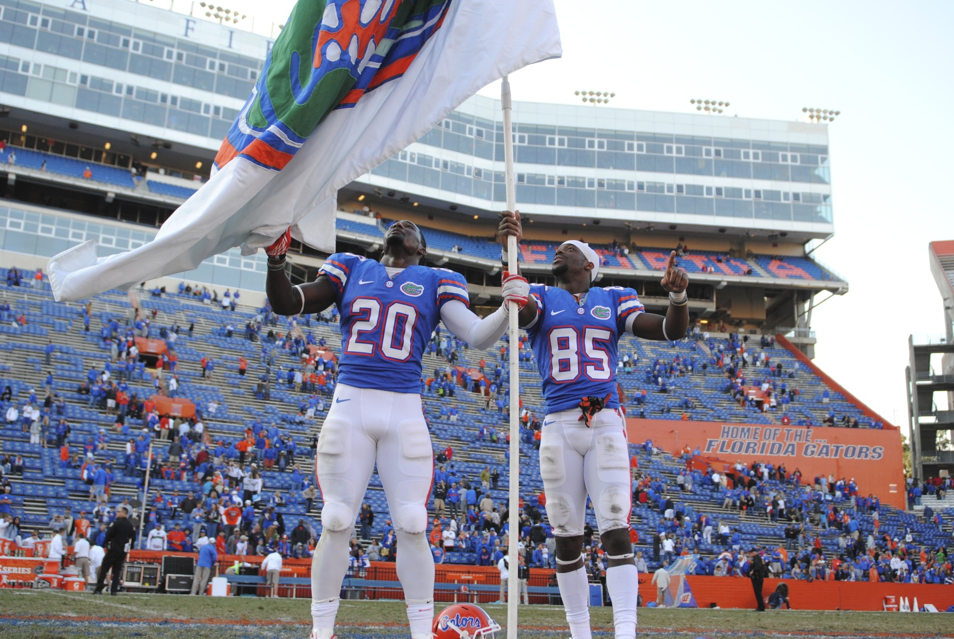 Seniors Omarius Hines (20) and Frankie Hammond Jr. (85) take pride in being Gators by holding a Gator flag after Saturday's game.