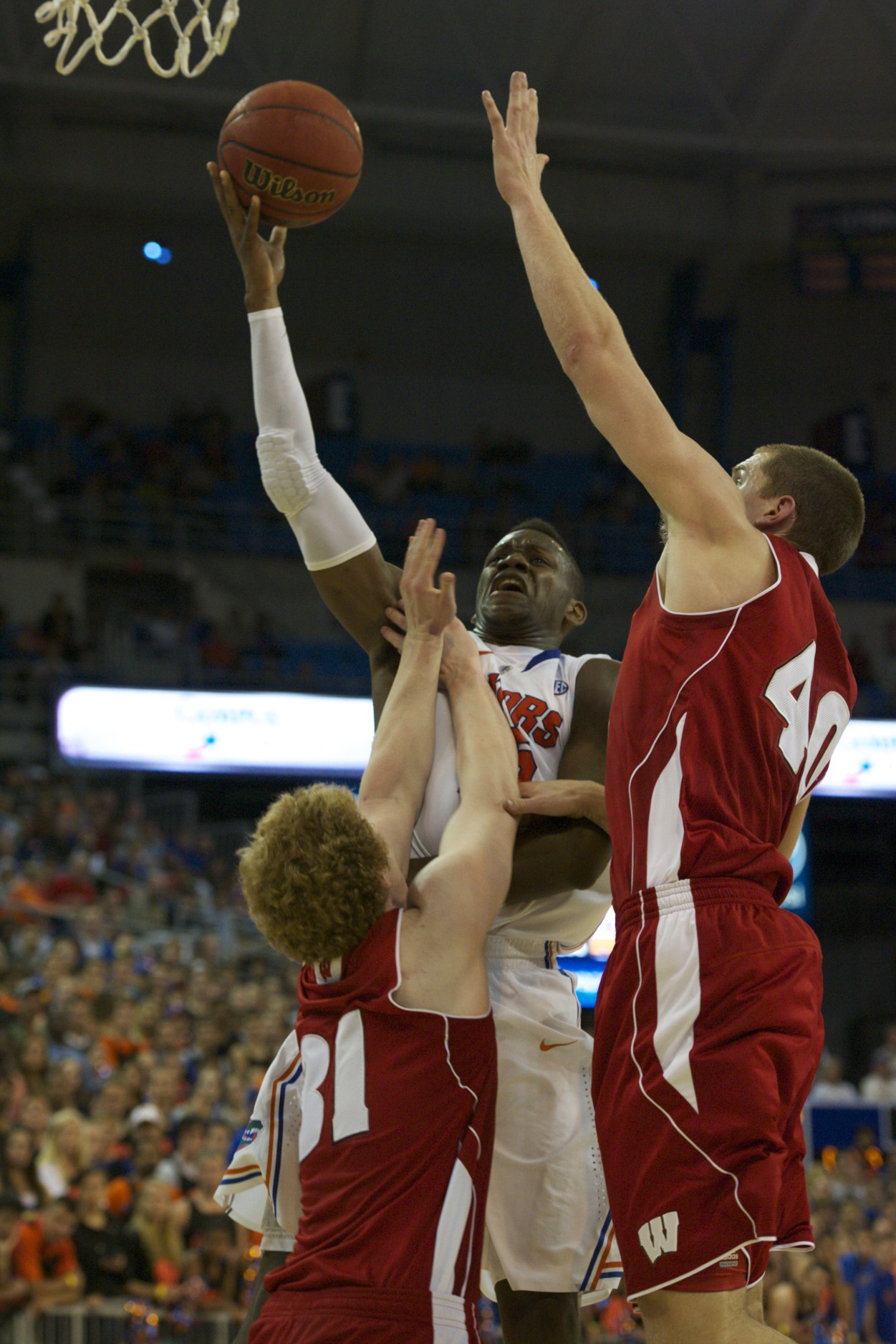 Will Yeguete (15) scores on two Wisconsin defenders in the first half of Wednesday's game.