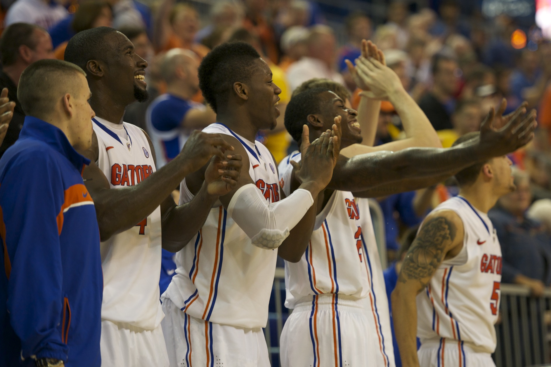 Patric Young (4), Will Yugete (15) and Casey Prather (24) cheer out the final seconds of the game from the bench Thursday night.
