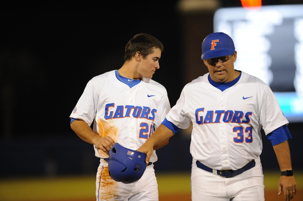 Cody Dent (20) gives his helmet and gloves to assistant coach Craig Bell after being the third out in an extra inning Friday night. The Gators lost to Ole Miss 4-3 Friday night in an 11-inning game at McKeethan Stadium.