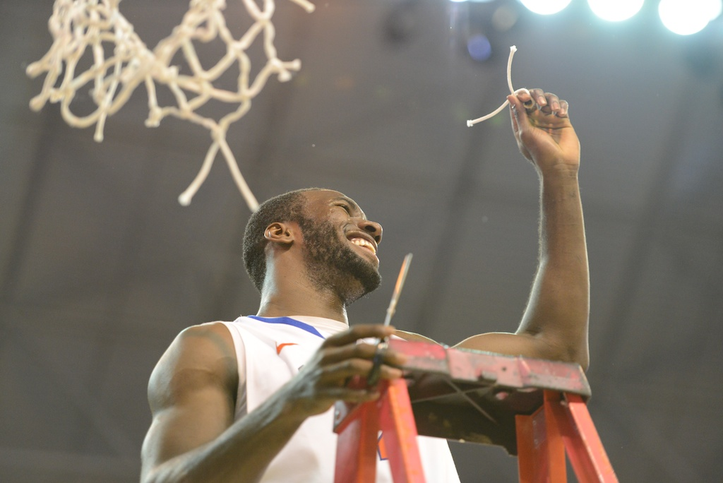 Patric Young (4) cuts a piece of the net Wednesday night after the Gators won the SEC title.