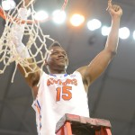 Will Yeguete (15) cuts a piece of the net Wednesday night after the Gators won the SEC title.