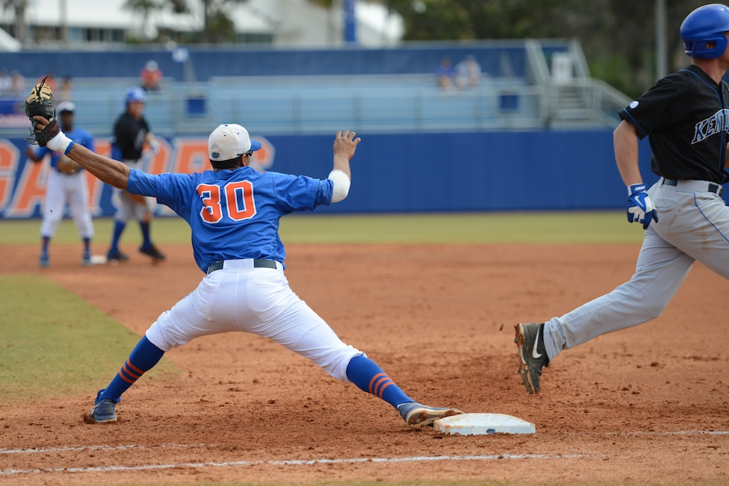 First baseman and senior Vickash Ramjit (30) gets a out for the Gators Sunday afternoon.