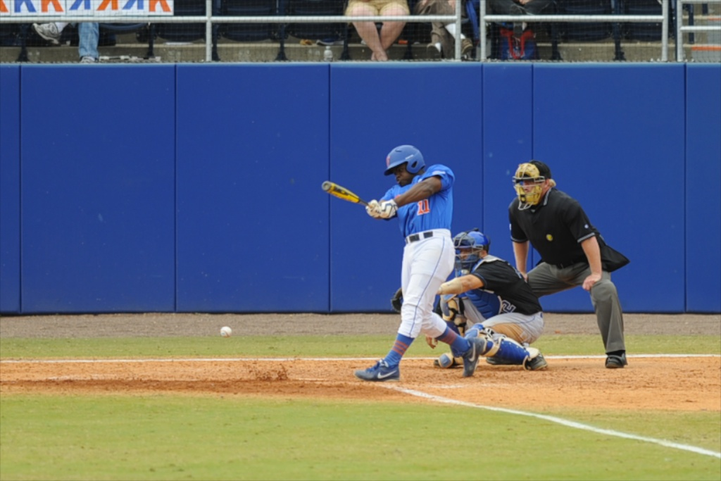 Josh Tobias (11) gets a hit for the Florida Gators Sunday.