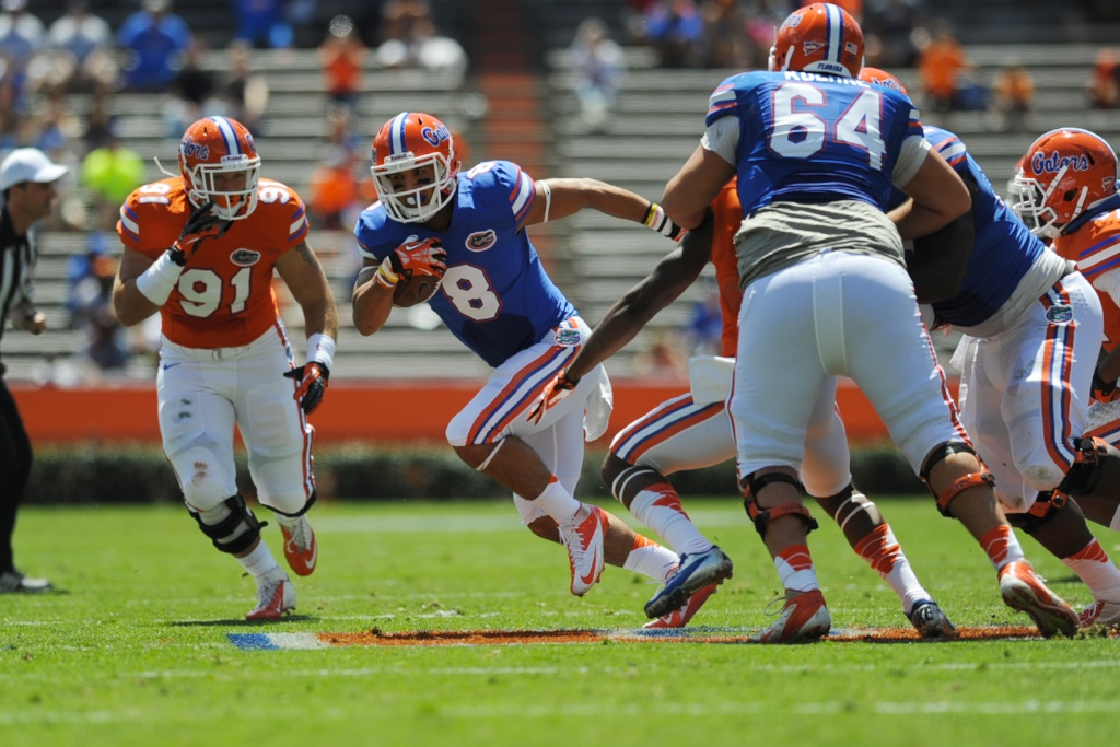 Running back Trey Burton (8) practices in a scrimmage Saturday afternoon at the Orange and Blue Debut.