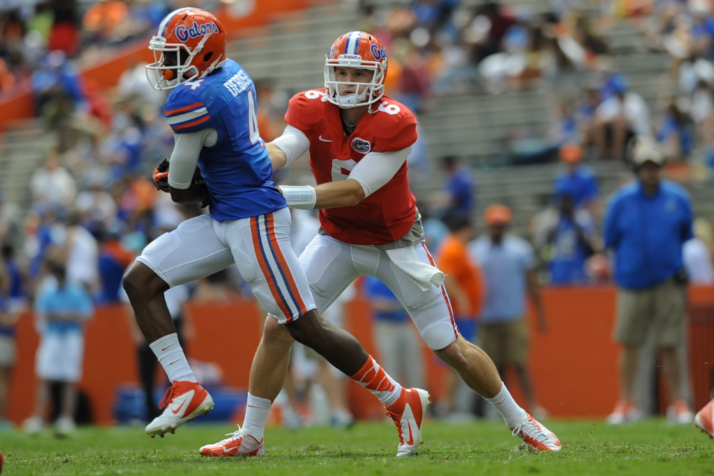 Quarterback Jeff Driskel (6) hands the ball off to wide reciever Andrew Debose (4) during a scrimmage Saturday afternoon at the Orange and Blue Debut.