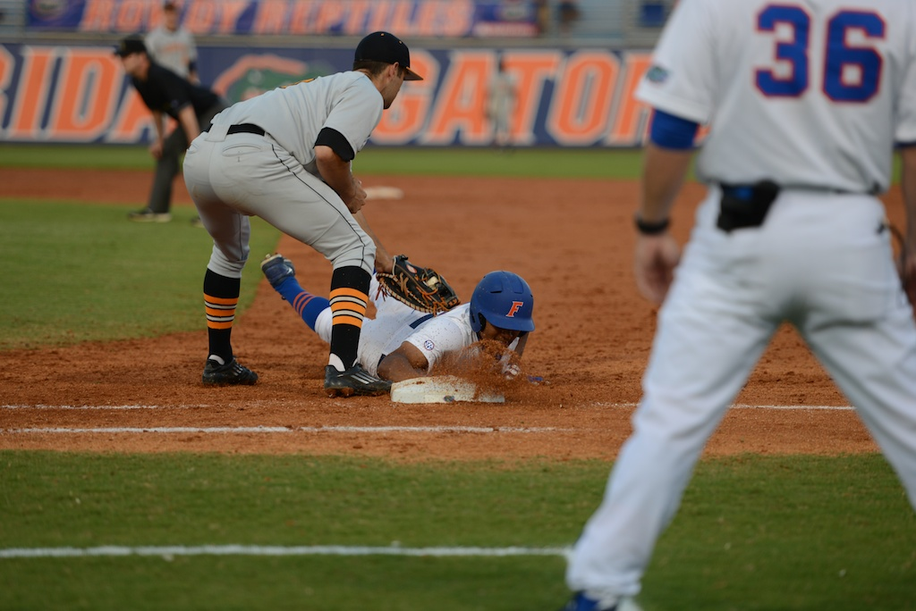Richie Martin (12) slides safely back to first base Friday. The Gators defeated the Vols 7-2 Friday night.