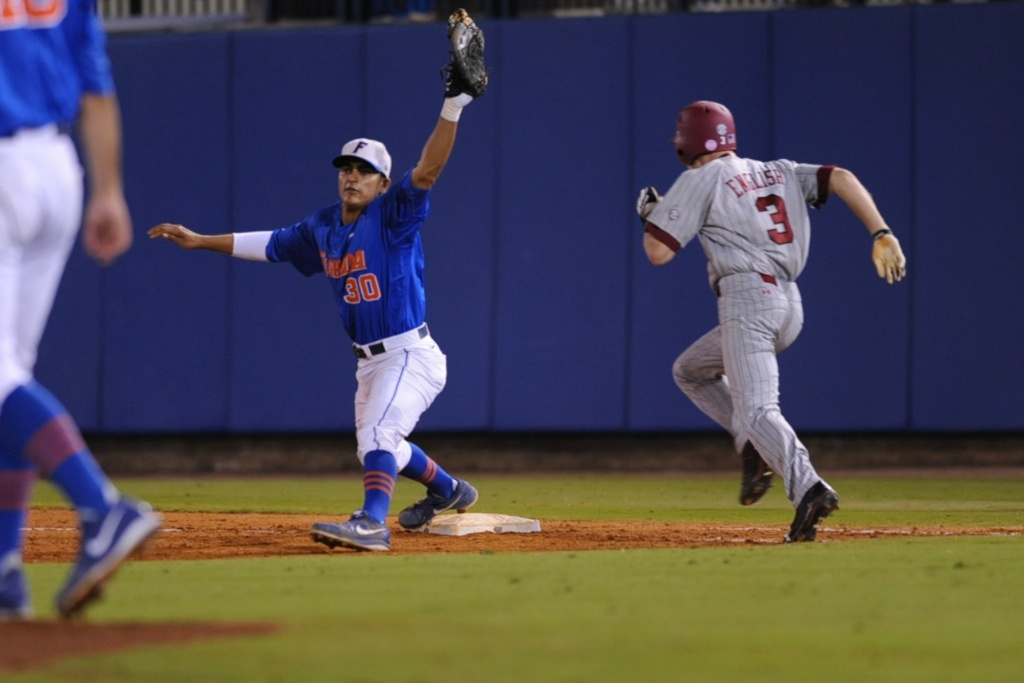 Vickash Ramjit (30) gets a runner out at first base Friday night. Florida defeated South Carolina 4-3 Friday night.