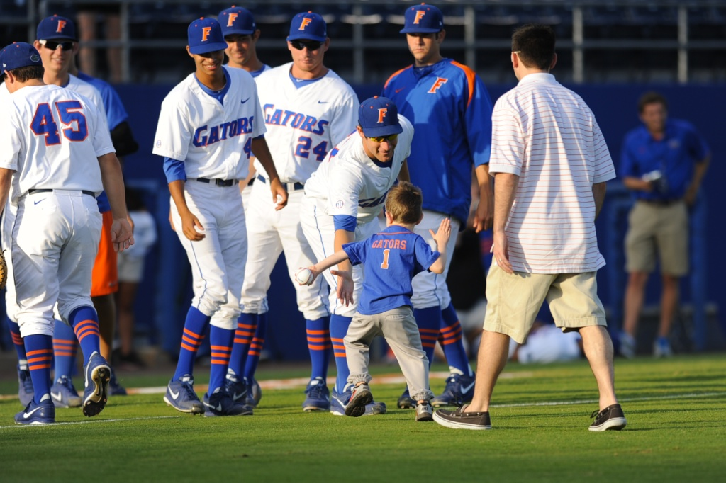 The members of the Florida Gators high-five the boy who threw the first pitch Friday. The Gators defeated the Vols 7-2 Friday night.