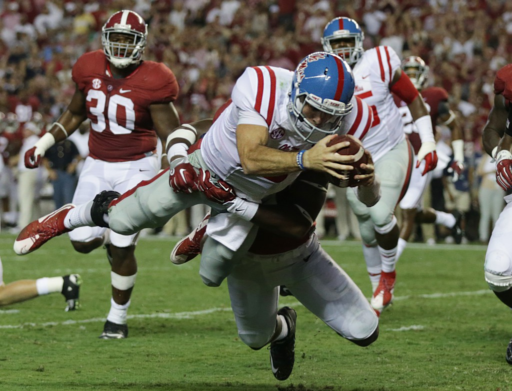 FILE - In this Sept. 19, 2015, file photo, Mississippi quarterback Chad Kelly dives in for a touchdown past Alabama linebacker Shaun Hamilton during first half of an NCAA college football game in Tuscaloosa, Ala. After leading East Mississippi Community College to a national title, Kelly transferred to Ole Miss, where he is ranked second nationally in passing efficiency. (AP Photo/Butch Dill, File)