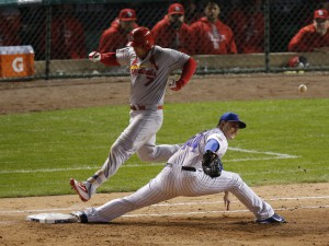 St. Louis Cardinals left fielder Matt Holliday (7) runs safely to the first base on a throwing error by Chicago Cubs second baseman Javier Baez (9) as first baseman Anthony Rizzo (44) can't misses the ball during the seventh inning of Game 3 in baseball's National League Division Series, Monday, Oct. 12, 2015, in Chicago. (AP Photo/Charles Rex Arbogast)