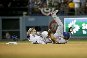 New York Mets shortstop Ruben Tejada, right, lands next to Los Angeles Dodgers' Chase Utley who broke up a double play during the seventh inning in Game 2 of baseball's National League Division Series, Saturday, Oct. 10, 2015 in Los Angeles. (AP Photo/Gregory Bull)