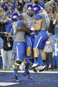 Kentucky quarterback Patrick Towles, center, celebrates his touchdown with teammates Kyle Meadows, left, and C.J. Conrad during the first half of an NCAA college football game against Missouri, Saturday, Sept. 26, 2015, in Lexington, Ky. (AP Photo/David Stephenson)
