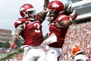 FILE - In this Sept. 5, 2015, file photo, Arkansas' Alex Collins (3) and Keon Hatcher (4) celebrate after Hatcher's touchdown during the NCAA college football game against UTEP at Donald W. Reynolds Razorback Stadium in Fayetteville, Ark. The Razorbacks beat the Miners, 48-13. (AP Photo/Samantha Baker, File)