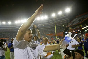Florida head coach Jim McElwain celebrates with the gator chomp in front of fans after defeating New Mexico State 61-13 in an NCAA college football game, Saturday, Sept. 5, 2015, in Gainesville, Fla. (AP Photo/John Raoux)