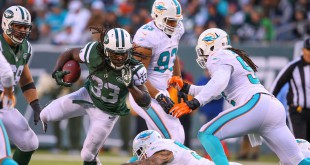 Nov 29, 2015; East Rutherford, NJ, USA; New York Jets running back Chris Ivory (33) avoids Miami Dolphins defenders and runs for a touchdown during the second half at MetLife Stadium.  The Jets defeated the Dolphins 38-20.  Mandatory Credit: Ed Mulholland-USA TODAY Sports