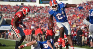 Florida running back Kelvin Taylor (21) leaps over teammate Jake McGee (83) to score a 3-yard touchdown in the second quarter. Taylor rushed for two touchdowns, and 121-yards on 25 carries. (Greenberry Taylor/WUFT News)