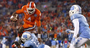 Dec 5, 2015; Charlotte, NC, USA; Clemson Tigers quarterback Deshaun Watson (4) carries the ball as North Carolina Tar Heels safety Donnie Miles (15) tackles during the second half in the ACC football championship game at Bank of America Stadium. Mandatory Credit: Joshua S. Kelly-USA TODAY Sports