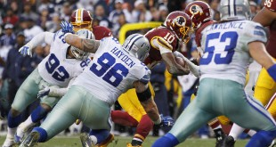 Dec 28, 2014; Landover, MD, USA; Washington Redskins quarterback Robert Griffin III (10) runs with the ball as Dallas Cowboys defensive tackle Nick Hayden (96) attempts the tackle in the fourth quarter at FedEx Field. The Cowboys won 44-17. Mandatory Credit: Geoff Burke-USA TODAY Sports
