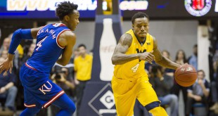 Jan 12, 2016; Morgantown, WV, USA; West Virginia Mountaineers guard Daxter Miles Jr. (4) dribbles past Kansas Jayhawks guard Devonte' Graham (4) during the second half at the WVU Coliseum. Mandatory Credit: Ben Queen-USA TODAY Sports