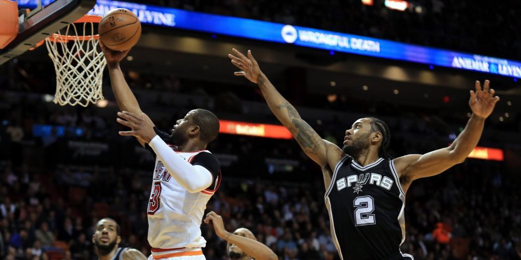 Feb 9, 2016; Miami, FL, USA; Miami Heat guard Dwyane Wade (3) scores past San Antonio Spurs forward Kawhi Leonard (2) during the first half at American Airlines Arena. Mandatory Credit: Steve Mitchell-USA TODAY Sports
