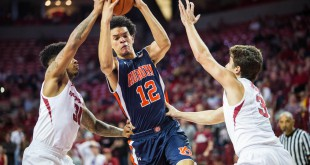 Feb 17, 2016; Fayetteville, AR, USA; Auburn Tigers forward Tyler Harris (12) moves to the basket between Arkansas Razorbacks guard Anton Beard (31) and Razorbacks guard Dusty Hannahs (3) during the second half of play at Bud Walton Arena. The Tigers won 90-86. Mandatory Credit: Gunnar Rathbun-USA TODAY Sports