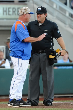 Jun 20, 2015; Omaha, NE, USA; Florida Gators head coach Kevin O'Sullivan talks with the umpire after his batter is called back to the plate after the umpires rules he did not try to avoid a pitch in the second inning against the Virginia Cavaliers in the 2015 College World Series at TD Ameritrade Park. Mandatory Credit: Steven Branscombe-USA TODAY Sports
