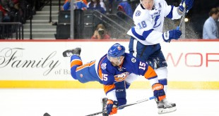 Apr 4, 2016; Brooklyn, NY, USA; New York Islanders right wing Cal Clutterbuck (15) is upended by Tampa Bay Lightning left wing Ondrej Palat (18) during the third period at Barclays Center. Mandatory Credit: Brad Penner-USA TODAY Sports