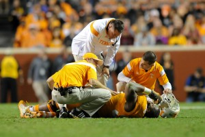 Oct 25, 2014; Knoxville, TN, USA; Tennessee Volunteers head coach Butch Jones check on an injured defensive lineman Trevarris Saulsberry (96) against the Alabama Crimson Tide during the second half at Neyland Stadium. Alabama won 34 to 20. Mandatory Credit: Randy Sartin-USA TODAY Sports