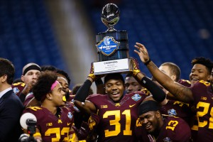 Dec 28, 2015; Detroit, MI, USA; Minnesota Golden Gophers defensive back Eric Murray (31) hold up the trophy after winning the Quick Lane Bowl against the Central Michigan Chippewas at Ford Field. Minnesota won 21-14. Mandatory Credit: Sage Osentoski-USA TODAY Sports