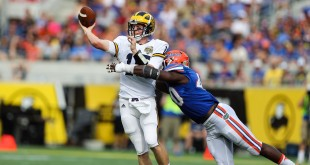 Jan 1, 2016; Orlando, FL, USA; Michigan Wolverines quarterback Jake Rudock (15) throws a pass as he pressured by Florida Gators linebacker Jarrad Davis (40) during the second quarter in the 2016 Citrus Bowl at Orlando Citrus Bowl Stadium. Mandatory Credit: Jim Dedmon-USA TODAY Sports