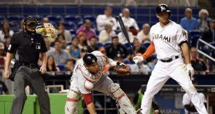 Apr 19, 2016; Miami, FL, USA; Washington Nationals catcher Wilson Ramos (40) reaches for wild pitch as Miami Marlins right fielder Giancarlo Stanton (27) looks on during the sixth inning at Marlins Park. Mandatory Credit: Steve Mitchell-USA TODAY Sports