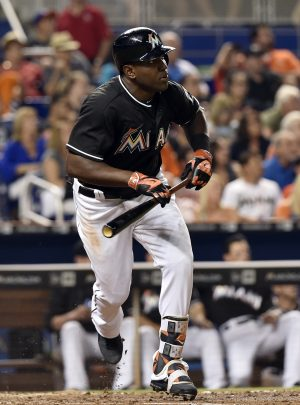 May 21, 2016; Miami, FL, USA; Miami Marlins center fielder Marcell Ozuna (13) connects for a triple during the sixth inning against the Washington Nationals at Marlins Park. Mandatory Credit: Steve Mitchell-USA TODAY Sports