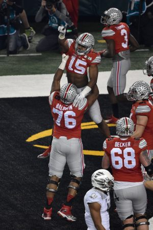 Jan 12, 2015; Arlington, TX, USA; Ohio State Buckeyes running back Ezekiel Elliott (15) and offensive lineman Darryl Baldwin (76) celebrate Elliot's touchdown against the Oregon Ducks during the game at AT&T Stadium. The Buckeyes defeated the Ducks 42-20. Mandatory Credit: Jerome Miron-USA TODAY Sports