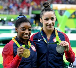 : Aug 11, 2016; Rio de Janeiro, Brazil; Simone Biles (USA) and Alexandra Raisman (USA) celebrate with their medals during the women's individual all-around final in the Rio 2016 Summer Olympic Games at Rio Olympic Arena. Mandatory Credit: Robert Hanashiro-USA TODAY Sports