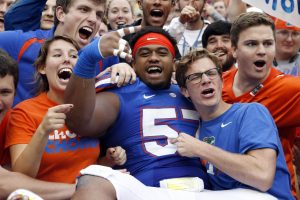 Nov 22, 2014; Gainesville, FL, USA; Florida Gators defensive lineman Caleb Brantley (57) jumps into the stands with fans after they beat the Eastern Kentucky Colonels at Ben Hill Griffin Stadium. Florida Gators defeated the Eastern Kentucky Colonels 52-3. Mandatory Credit: Kim Klement-USA TODAY Sports