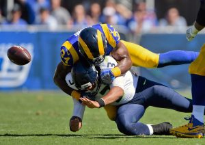 Sep 18, 2016; Los Angeles, CA, USA; Seattle Seahawks quarterback Russell Wilson (3) looses the ball as he is sacked by Los Angeles Rams defensive end Robert Quinn (94) during the first half of a NFL game against the Seattle Seahawks at Los Angeles Memorial Coliseum. Mandatory Credit: Kirby Lee-USA TODAY Sports