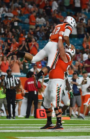 Sep 3, 2016; Miami Gardens, FL, USA; Miami Hurricanes offensive lineman Hunter Knighton (54) lifts quarterback Malik Rosier (12) to celebrate after his touchdown against the Florida A&M Rattlers during the second half at Hard Rock Stadium. The Miami Hurricanes defeat the Florida A&M Rattlers 70-3. Mandatory Credit: Jasen Vinlove-USA TODAY Sports