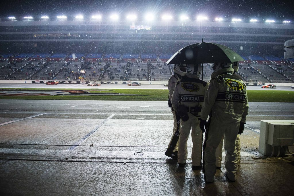 Nov 6, 2016; Fort Worth, TX, USA; NASCAR officials huddle under an umbrella as Sprint Cup Series driver Carl Edwards (19) and driver Joey Logano (22) drive by in the rain during the AAA Texas 500 at Texas Motor Speedway. Mandatory Credit: Jerome Miron-USA TODAY Sports