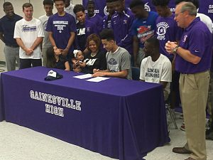 Coach Kelly Beckham (Far Right) watches former player sign letter of content.
