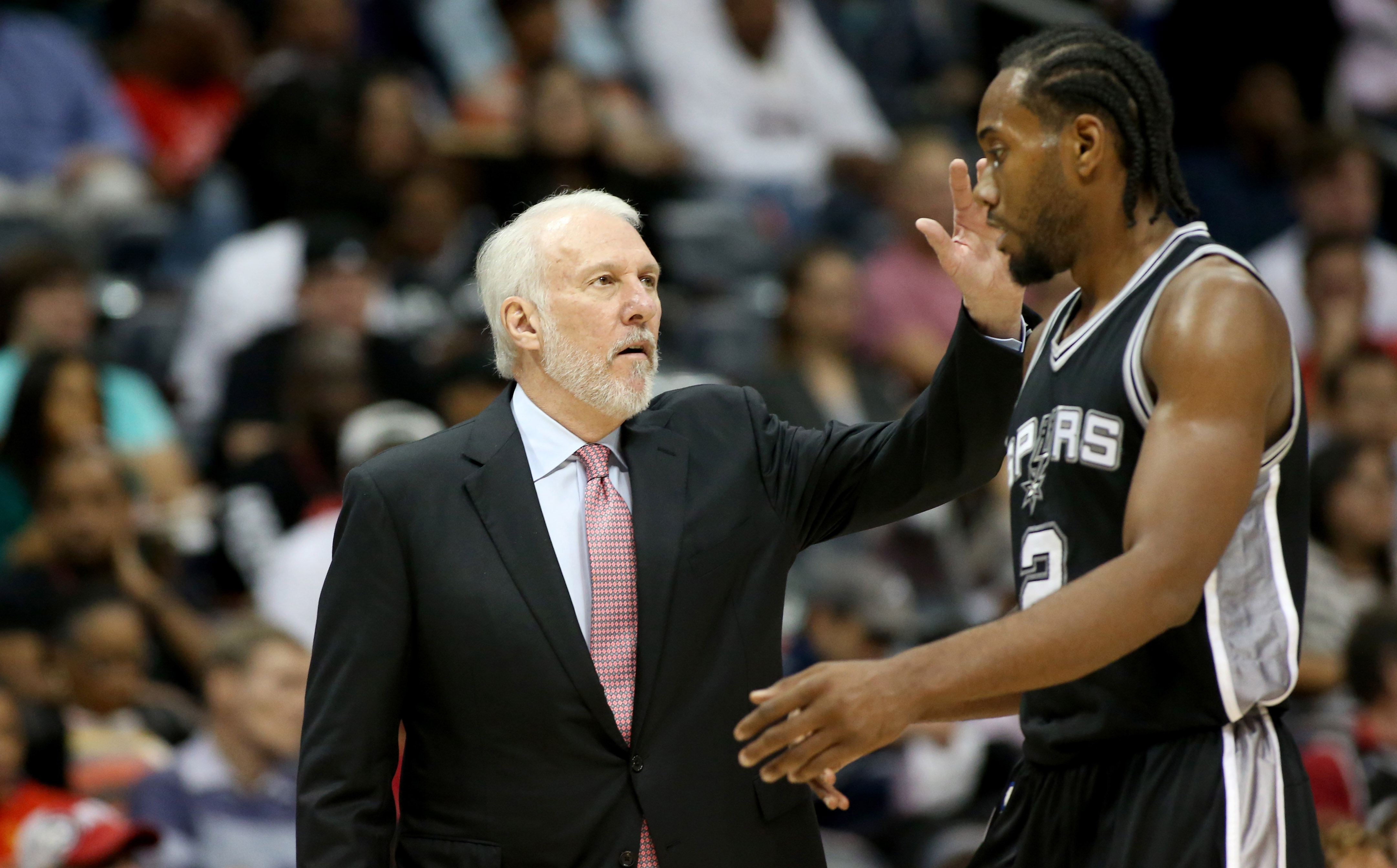 Oct 14, 2015; Atlanta, GA, USA; San Antonio Spurs head coach Gregg Popovich greets forward Kawhi Leonard (2) as he walk to the bench in the third quarter of their game against the Atlanta Hawks at Philips Arena. The Hawks won 100-86. Mandatory Credit: Jason Getz-USA TODAY Sports